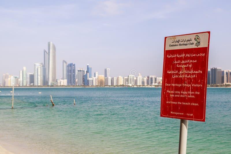 Rött varnande bräde som förbjuder simning i havet på territoriet av emiratarvbyn på bakgrunden av havet och staden arkivfoto