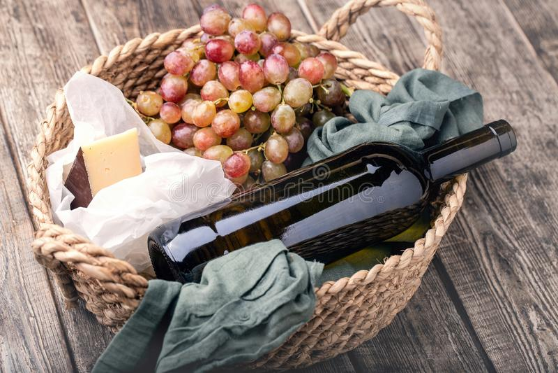 Rött vin, druvor och ost i korg arkivfoto