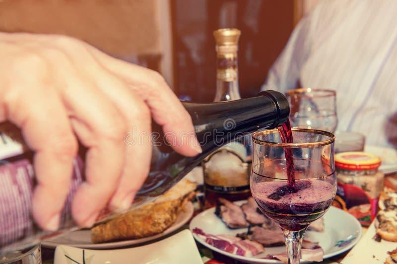 Rött vin flödar in i exponeringsglaset i aftonen på matställen med vänner royaltyfria bilder