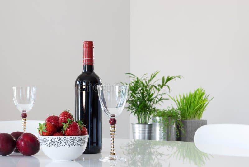 Rött vin, frukter och eleganta exponeringsglas arkivfoto