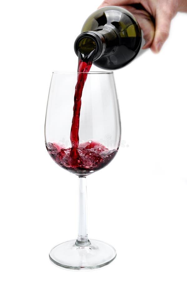 Rött vin hällde från en flaska i en elegant crystal bägare, isola arkivbild