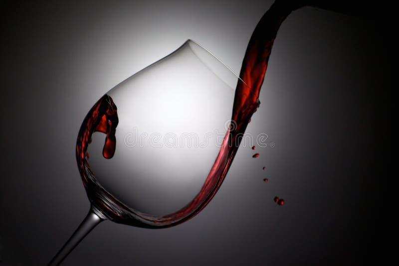 Rött vin hällde in i ett vinexponeringsglas med droppar royaltyfri bild