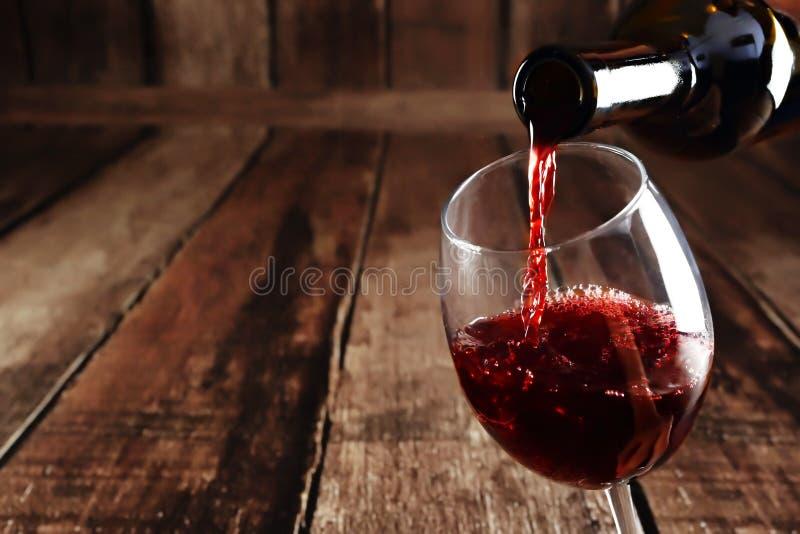 Rött vin hälls från flaskan till exponeringsglas arkivfoto