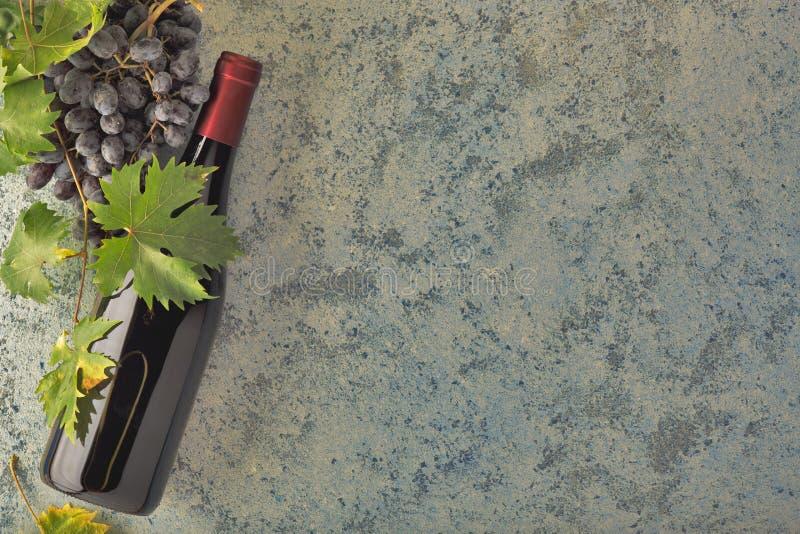 Rött vin i en flaska, druvor, kork och druvasidor på en filial arkivfoton