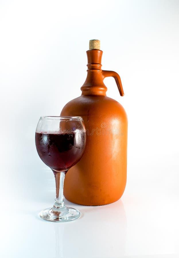 Rött vin i ett exponeringsglas av vin bredvid behållaren royaltyfri foto