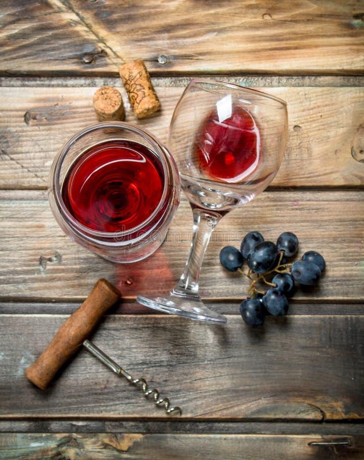 Rött vin i ett exponeringsglas med druvor och en korkskruv arkivfoto
