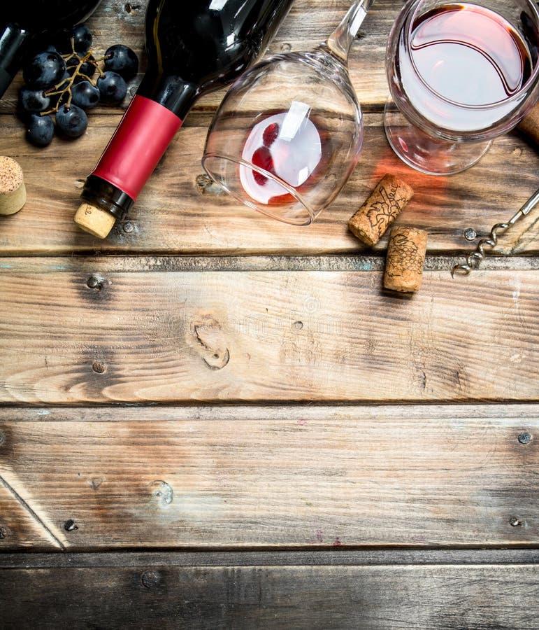Rött vin i ett exponeringsglas med druvor och en korkskruv arkivbilder