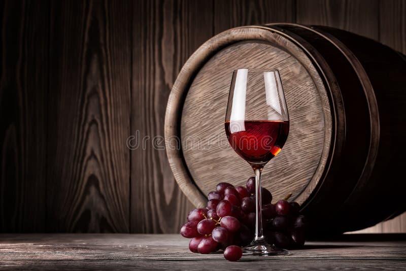 Rött vin i exponeringsglas och grupp av druvor royaltyfria foton