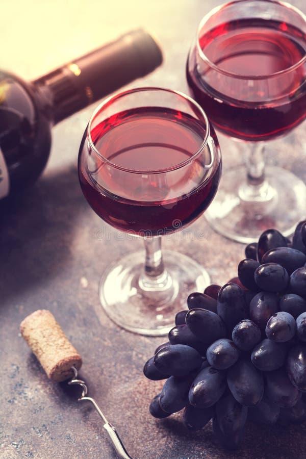 Rött vin i exponeringsglas i solljuset, druvor, en flaska, en kork, en korkskruv Selektivt fokusera tonat foto arkivbild
