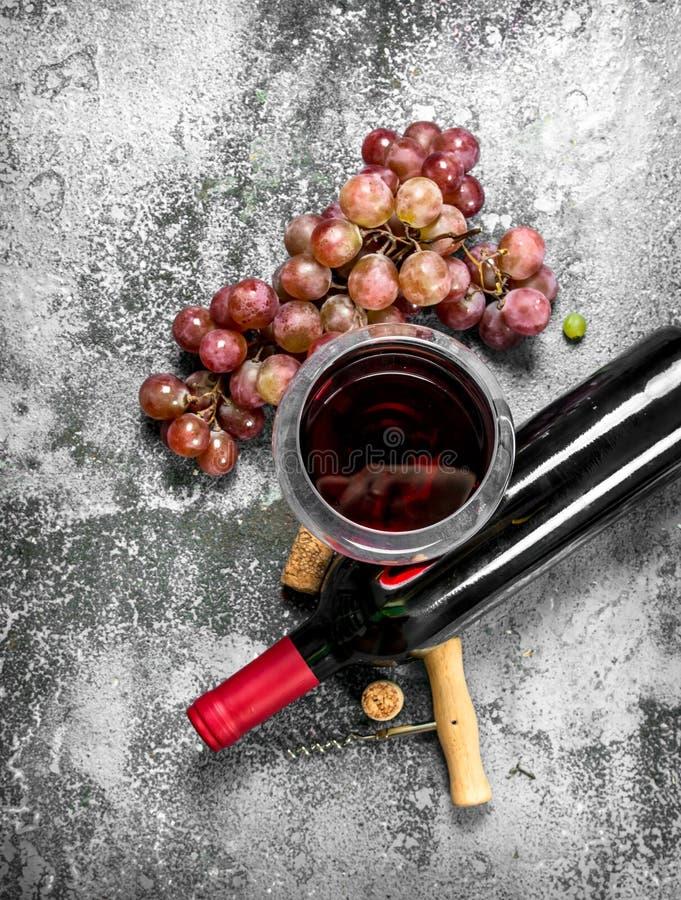 Rött vin med en korkskruv royaltyfria bilder