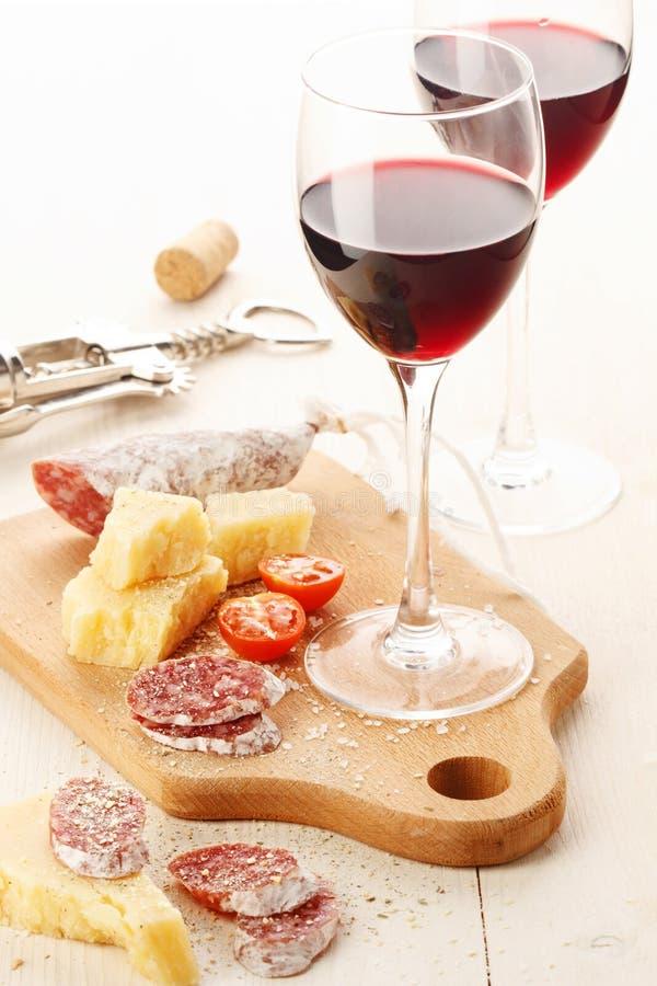 Rött vin och sortiment av mellanmål royaltyfria foton