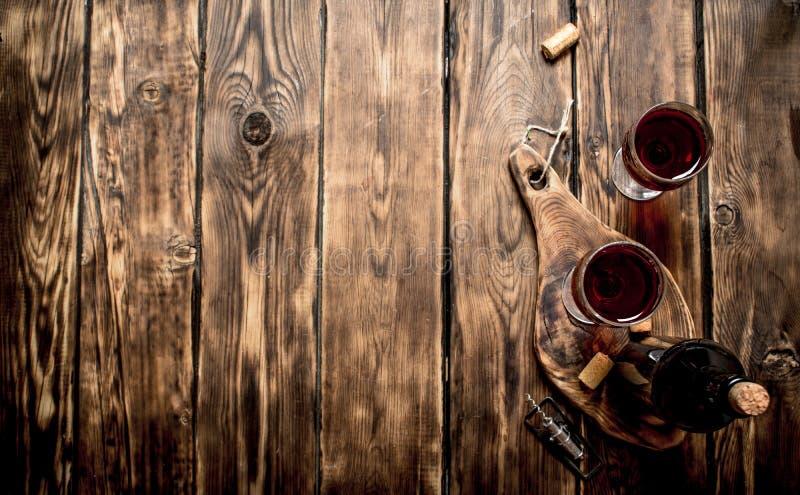 Rött vin på träbräde med proppar och en korkskruv arkivbild