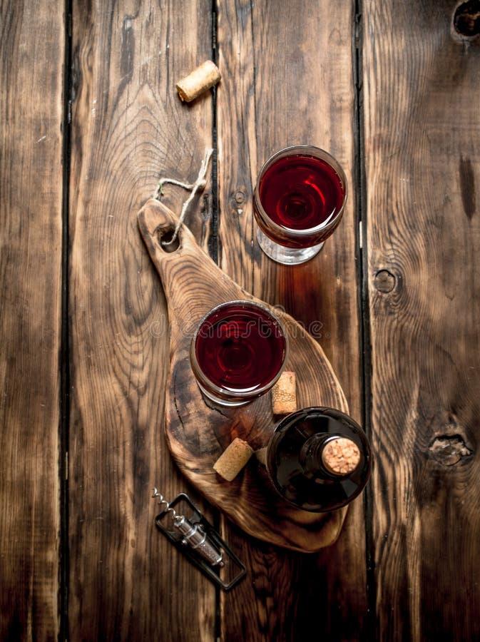 Rött vin på träbräde med proppar och en korkskruv royaltyfri foto
