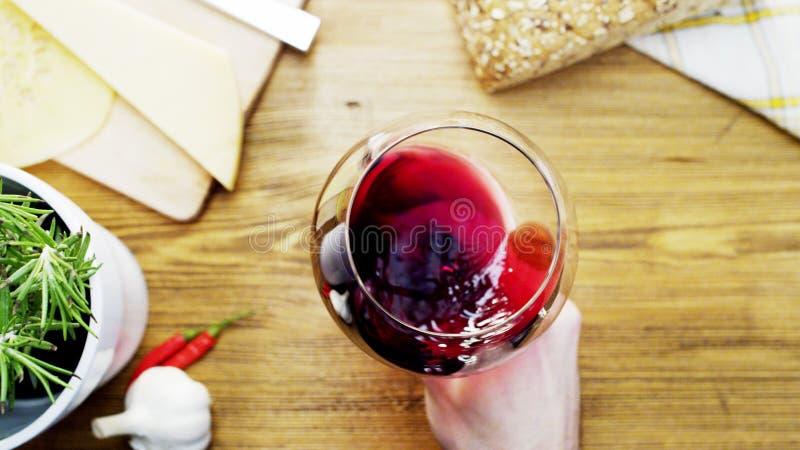 Rött vin som är rörande upp i en Glass Holded av en man royaltyfria foton