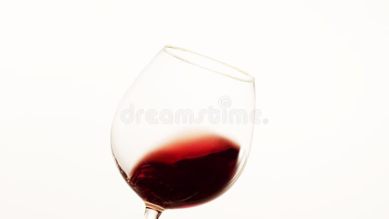 Rött vin som flyttar sig till rätsidan av ett exponeringsglas arkivfoton