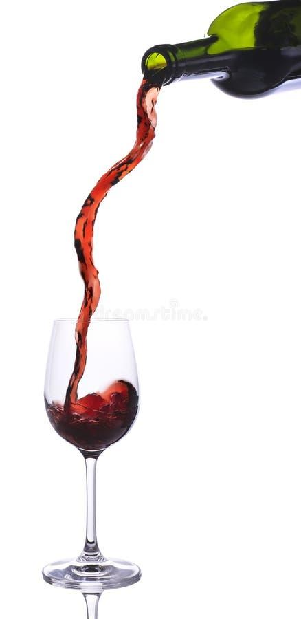 Rött vin som häller från lång ström för flaska royaltyfri foto
