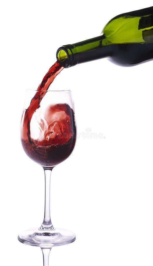 Rött vin som häller in i den lilla vinglaset royaltyfri foto