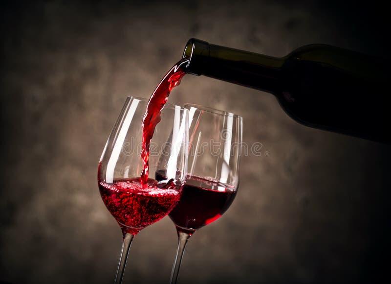 Rött vin som häller in i exponeringsglas från flaskan royaltyfria foton