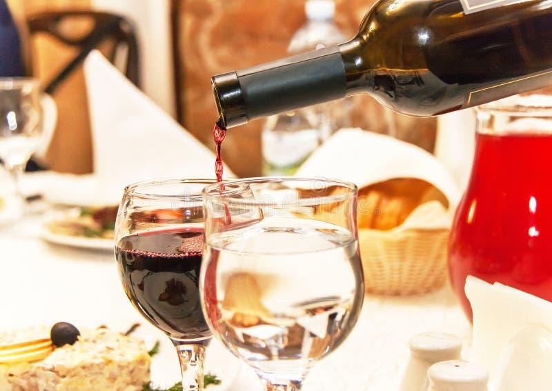 Rött vin som häller in i vinexponeringsglas, det anseende på tabellen royaltyfri foto