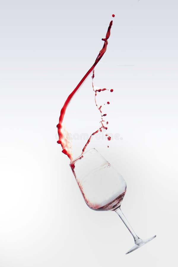 Rött vin som plaskar ut ur ett exponeringsglas som isoleras över vit bakgrund royaltyfri fotografi