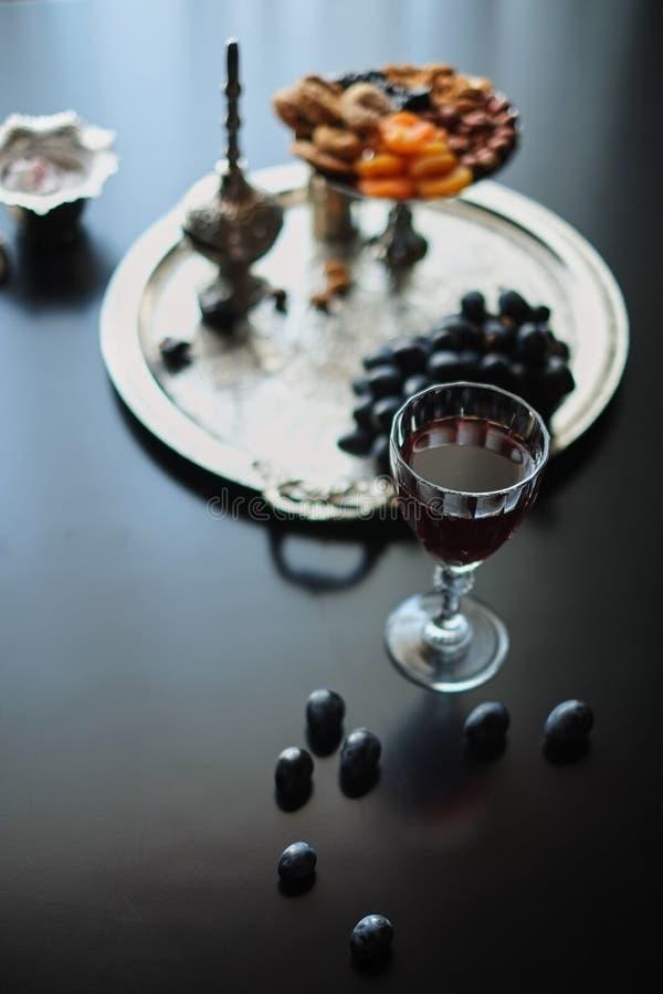 Rött vin, vinglas med valnötter, druvor och fikonträd på mörk träbakgrund royaltyfria bilder