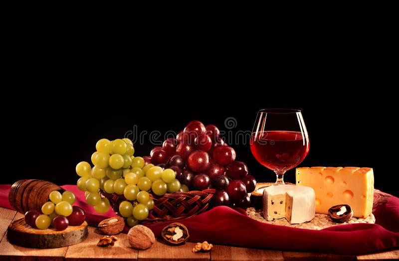 Rött vinexponeringsglas med ost, druvor och muttrar fotografering för bildbyråer