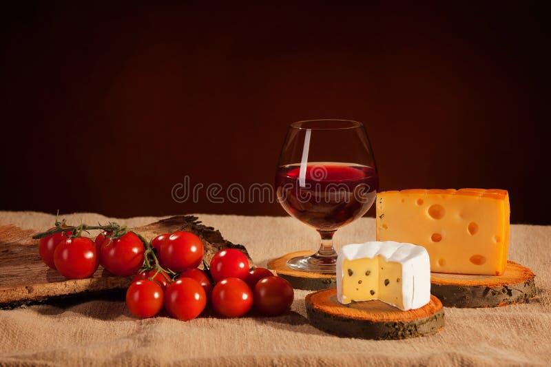 Rött vinexponeringsglas med ost och tomater royaltyfria bilder