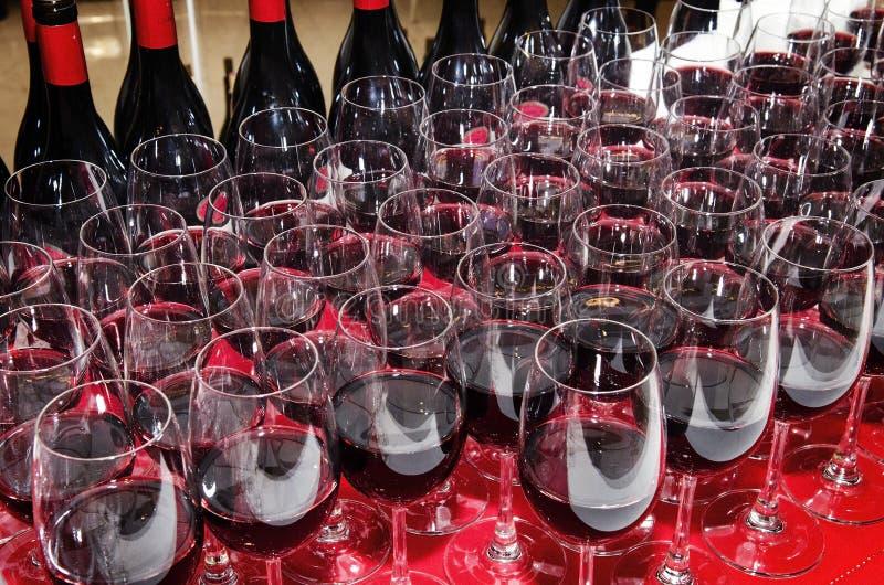Rött vinexponeringsglas och buteljerar arkivbilder