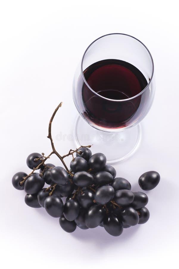 Rött vinexponeringsglas och druvor från överkant royaltyfri bild