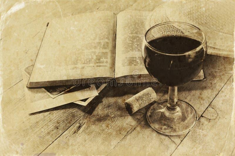 Rött vinexponeringsglas och gammal bok på trätabellen tappning filtrerad bild Svartvitt stilfoto royaltyfria foton