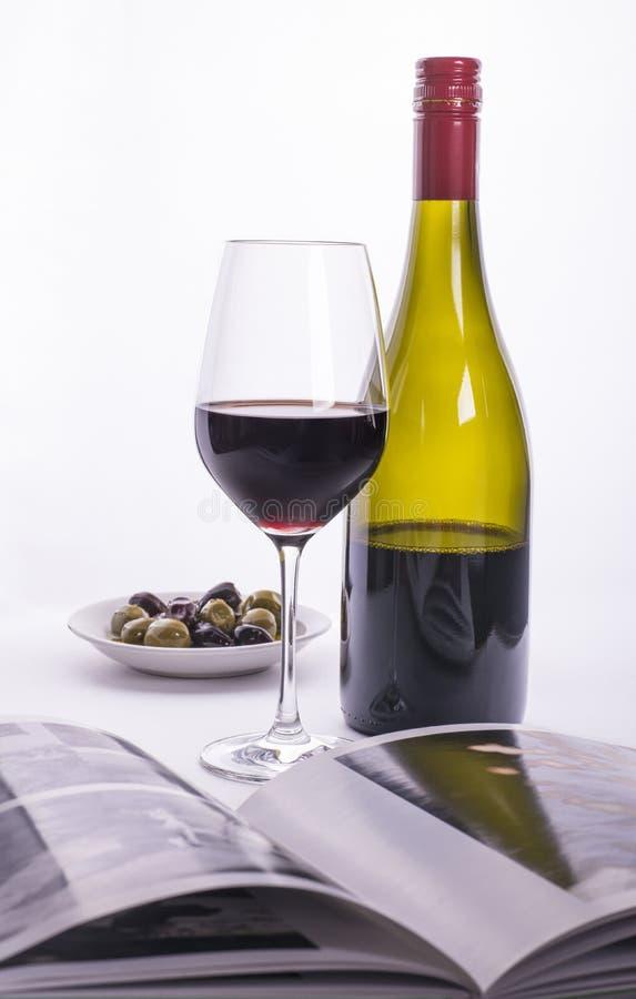 Rött vinflaska, exponeringsglas, oliv och bok arkivfoton