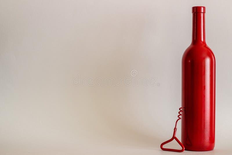 Rött vinflaska och en korkskruv Gr? f?rgbakgrund minimalism royaltyfri foto