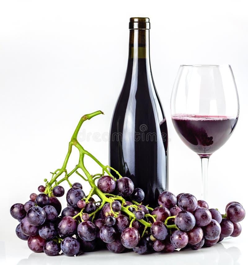 Rött vinflaska, vinglas och druvor fotografering för bildbyråer
