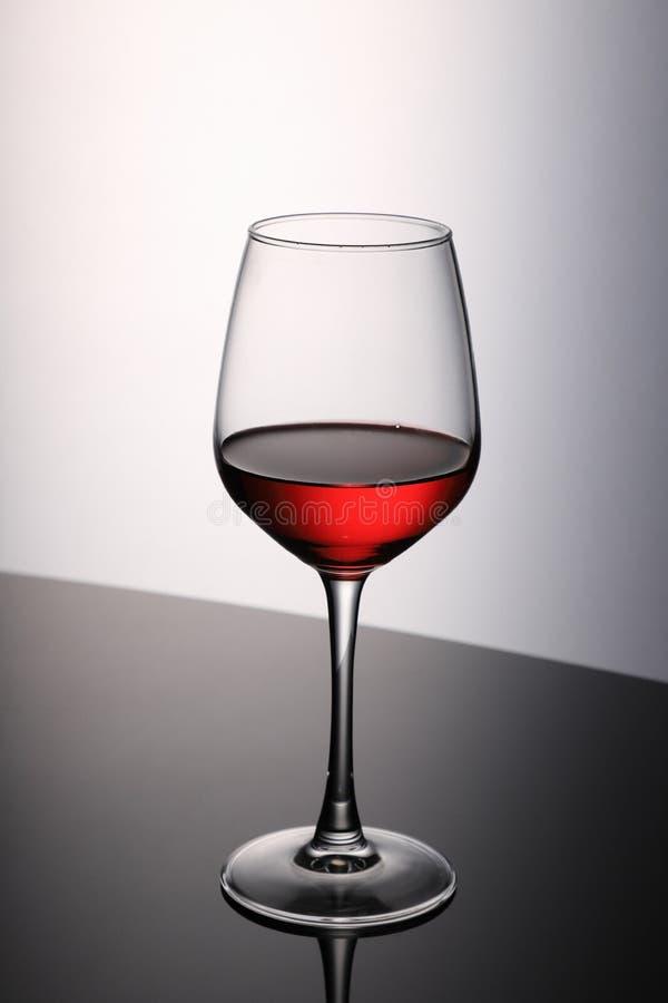 Rött vinglas på svart bord med reflektion arkivbilder