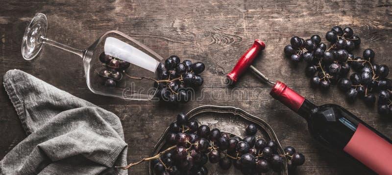Rött vinstilleben med flaskan och tappningkorkskruv, exponeringsglas och druvor på åldrig träbakgrund royaltyfria foton