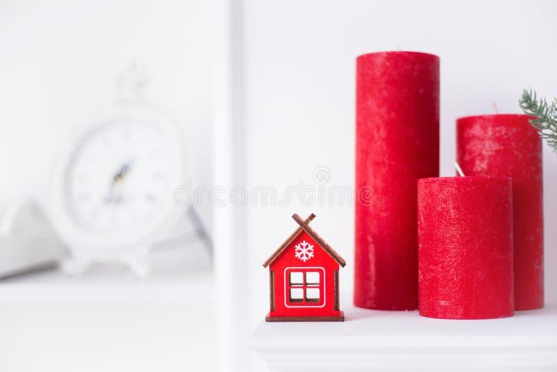 Rött vinterhus för leksak i hem- festlig inre med julljus och den vita väggen på bakgrund royaltyfri fotografi