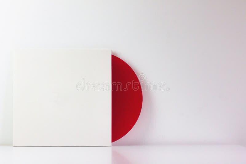Rött vinylrekord, i dess vita ask, med tomt utrymme som ska skrivas Med vit bakgrund Minimalist foto arkivbilder