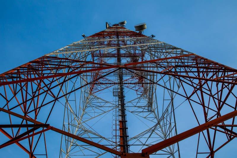 Rött vitt telekommunikationtorn mot blå himmel - nedersta sikt royaltyfri fotografi