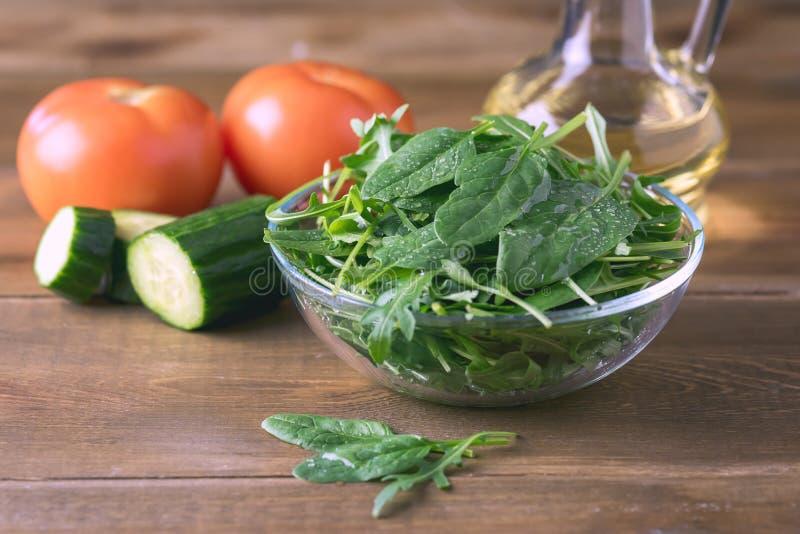 Rúcula e salada frescas dos espinafres no fundo de madeira rústico Olive Oil Toned Healthy Food imagens de stock royalty free