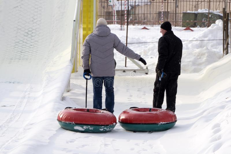 Rússia Berezniki 2 de fevereiro de 2018: Dois homens novos com uma trouxa e para ir tubulação nas madeiras do inverno imagens de stock