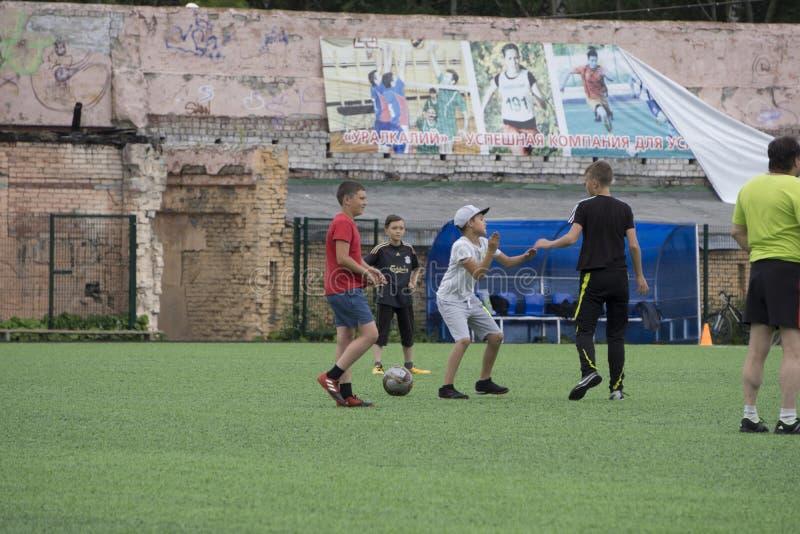 Rússia - Berezniki o 25 de julho de 2017: Os rapazes pequenos caçoam o futebol interno do jogo na zona aberta na cidade Junior Ch fotografia de stock royalty free