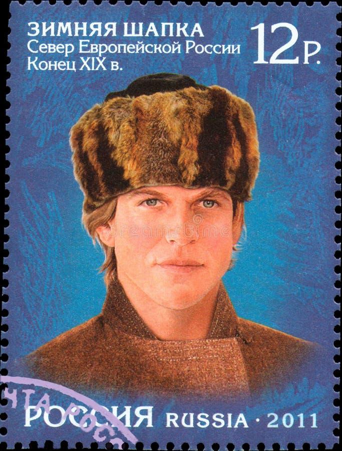 RÚSSIA - CERCA DE 2011: selo impresso em Rússia, mostras um homem em uma mantilha do norte do russo, chapéu do inverno fotografia de stock royalty free
