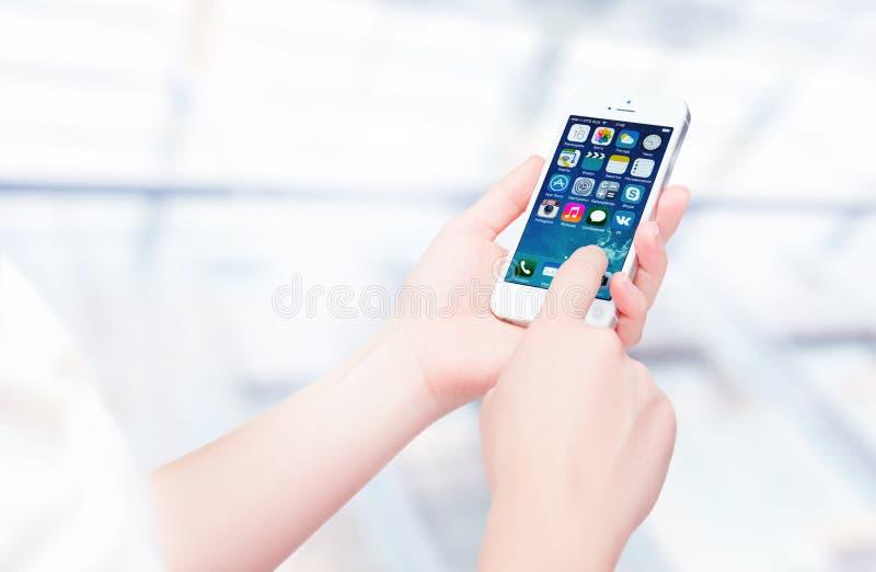 Rússia, Chelyabinsk, o 8 de setembro de 2014 Pessoa que guarda um iPhone branco novo 5S de Apple, smartphone na parte da linha do fotografia de stock royalty free