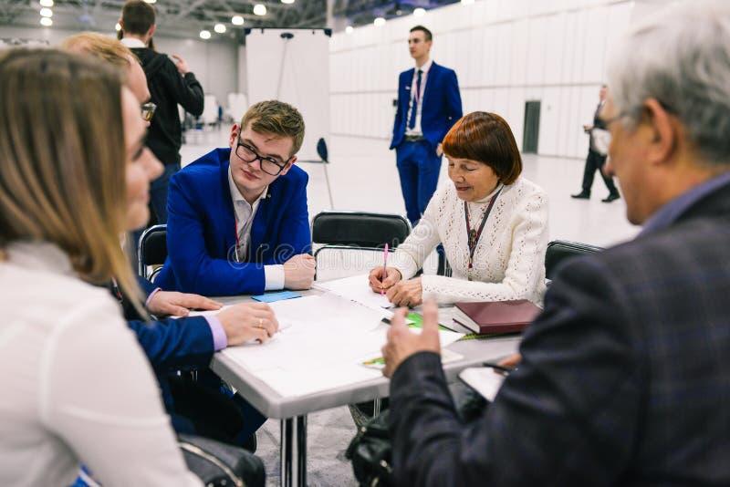 Rússia, cidade Moscou - 18 de dezembro de 2017: Os homens e as mulheres condenam o projeto na reunião Os homens de negócios da foto de stock