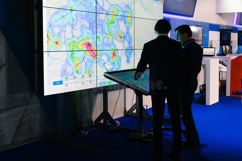 Rússia, cidade Moscou - 18 de dezembro de 2017: Os homens de negócios novos estão estando perto de um grande tela táctil Os h imagens de stock royalty free