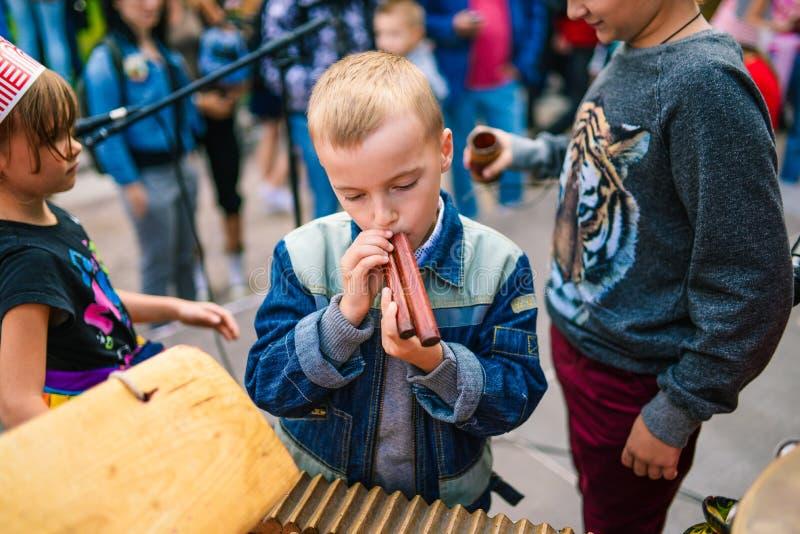 R?ssia, cidade Moscou - 6 de setembro de 2014: As brincadeiras um instrumento musical O menino guarda um acordo de madeira em sua imagens de stock royalty free