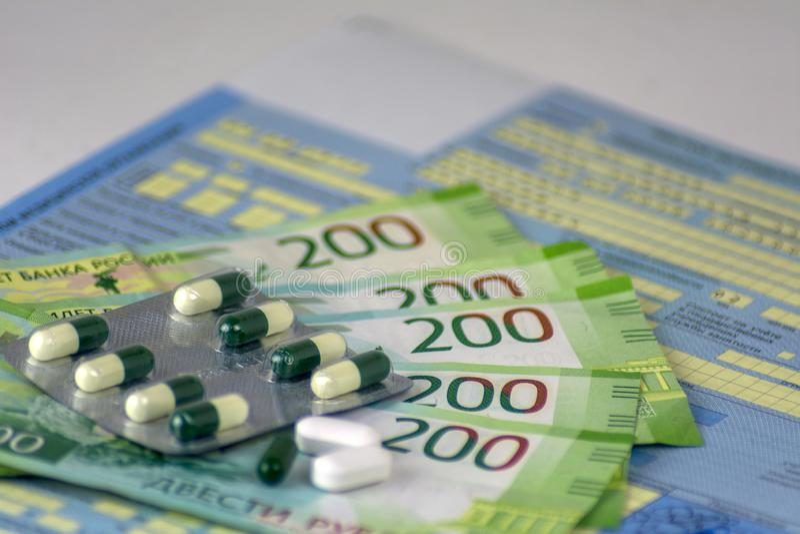 Rússia Close-up, baixa médica do russo com selos A garrafa dos comprimidos e dos alguns comprimidos no volume Dinheiro-cédulas do foto de stock