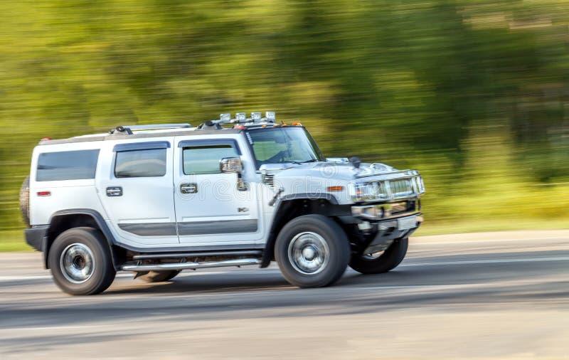 Rússia, Irkutsk - 20 de agosto de 2015: O carro grande de prata de Hummer monta acima da estrada na alta velocidade fotografia de stock