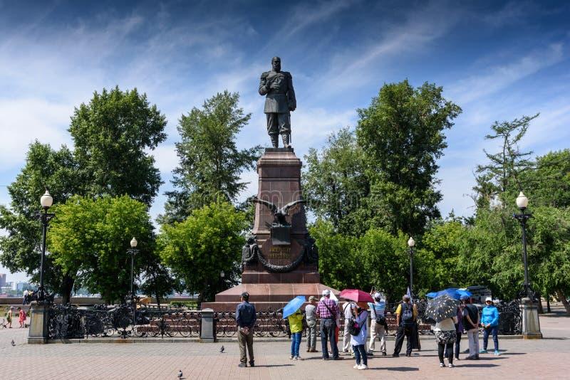 Rússia, Irkutsk - 6 de julho de 2019: os turistas com guarda-chuvas olham o monumento de Alexander III Imperador do Todo-russo foto de stock