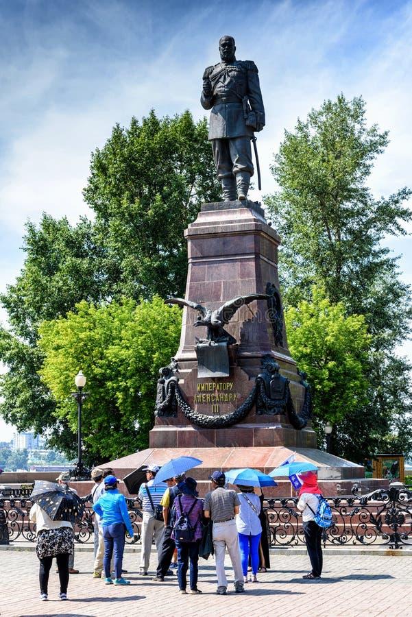 Rússia, Irkutsk - 6 de julho de 2019: os turistas com guarda-chuvas olham o monumento de Alexander III Imperador do Todo-russo fotografia de stock royalty free